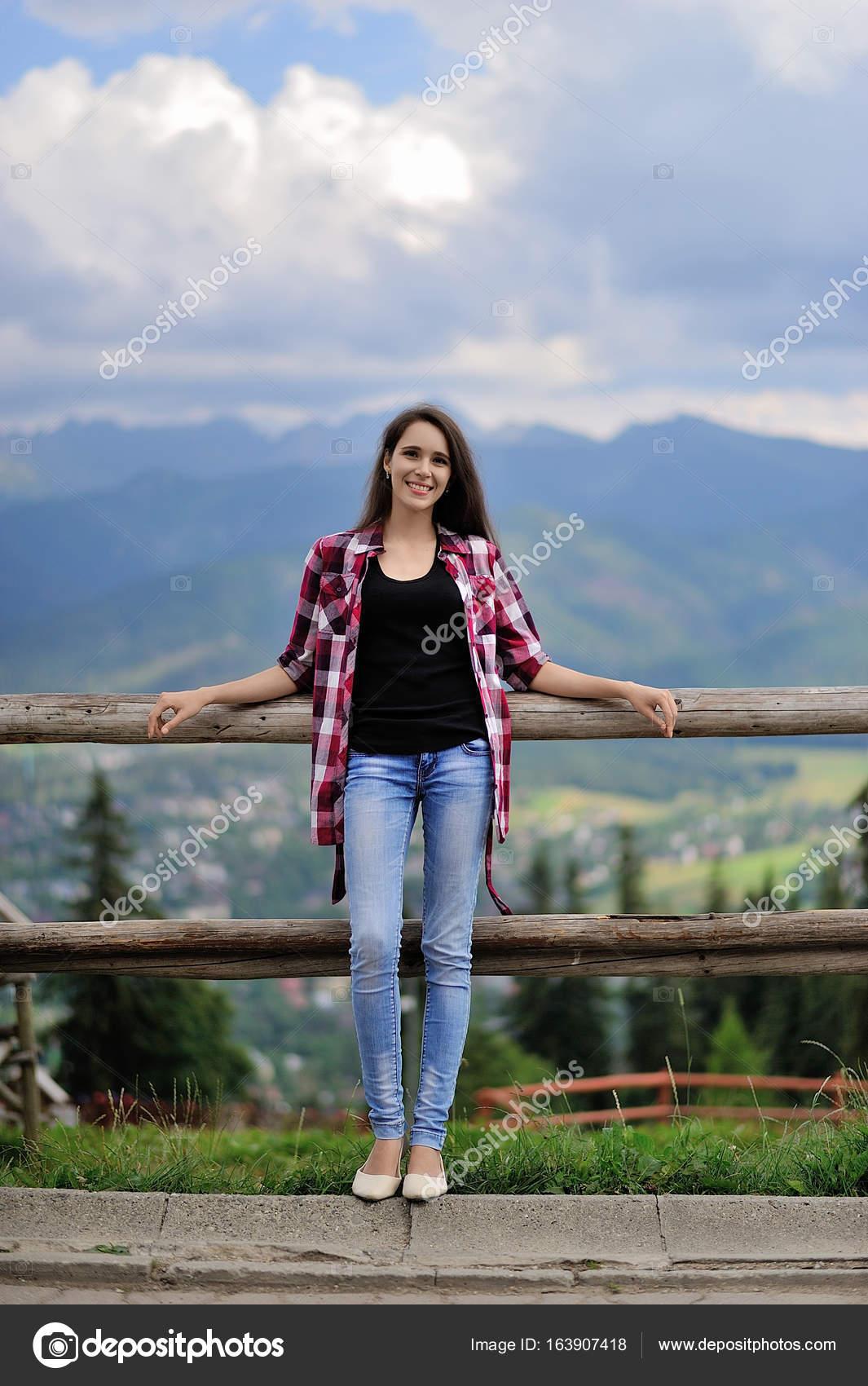 heureuse jeune fille assise sur une cl ture sur un fond de montagnes zako photographie. Black Bedroom Furniture Sets. Home Design Ideas