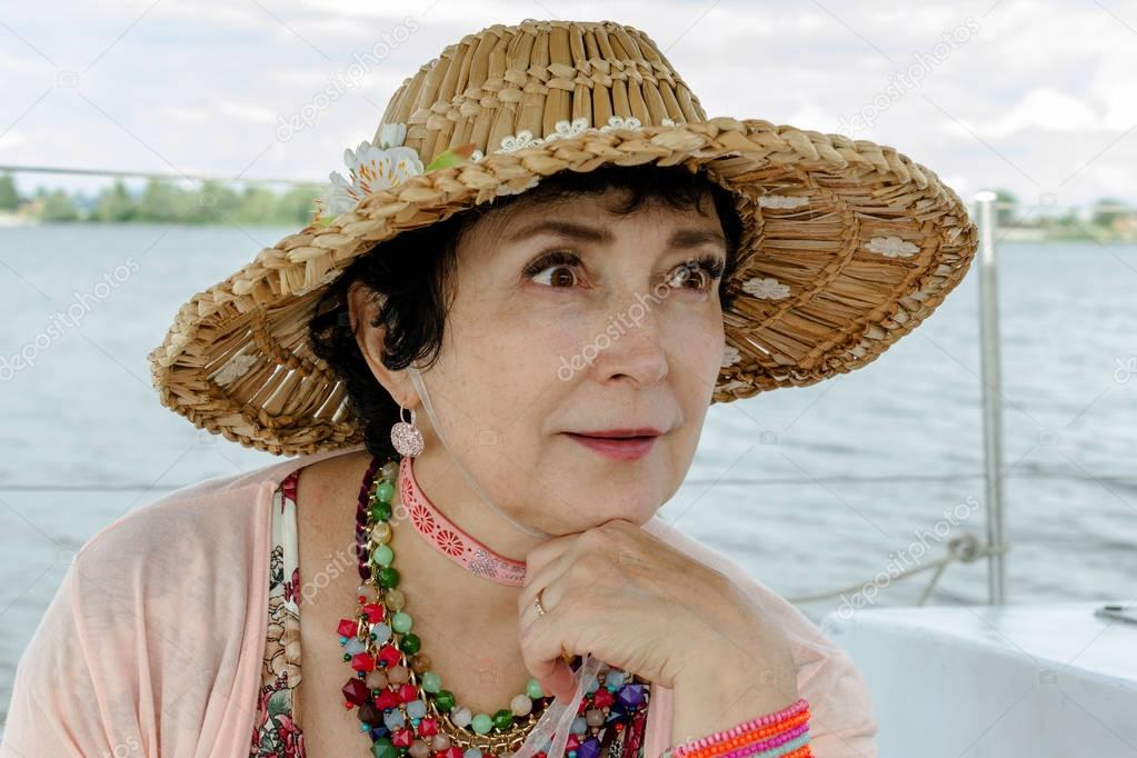 Woman aged, wearing a straw hat on the background of water.
