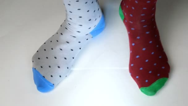 Human legs in fashionable socks of different colors move on white solid surface, walk and stomp on spot. Maybe he is dancing, doing sports or fitness. Close-up.