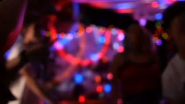 Fun party. Group of friends are relaxing, dancing and having fun in nightclub or musical concert. Abstract defocused background. Blurred motion.