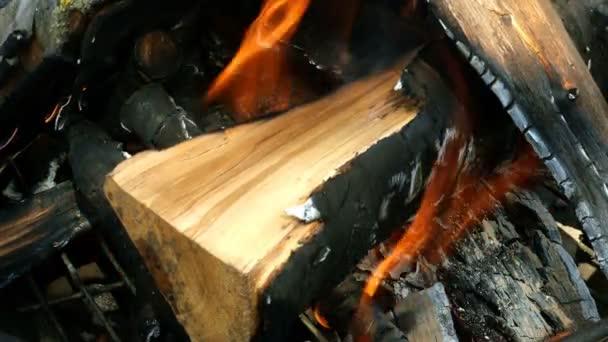 Brennholz und Kohle im Kamin verbrennen. Heißer Hintergrund mit orangefarbener Flamme Hintergrund des Feuers. Nahaufnahme.