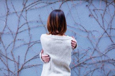 beautiful young woman hugging herself