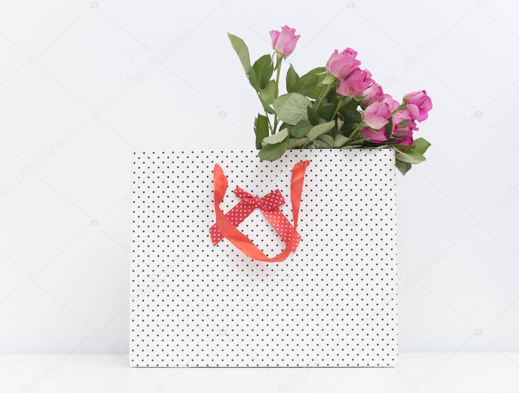 pink roses in dotted shopping bag