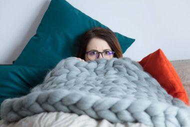 woman hiding in her blanket