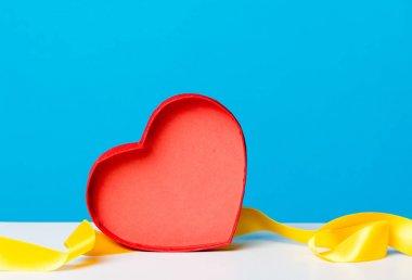 red heart shape box and  ribbon
