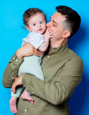 Young father and son on blue background