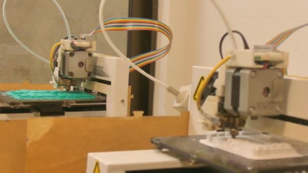 Two-shot of a pair of generic unbranded 3D printers at work in a coworking space