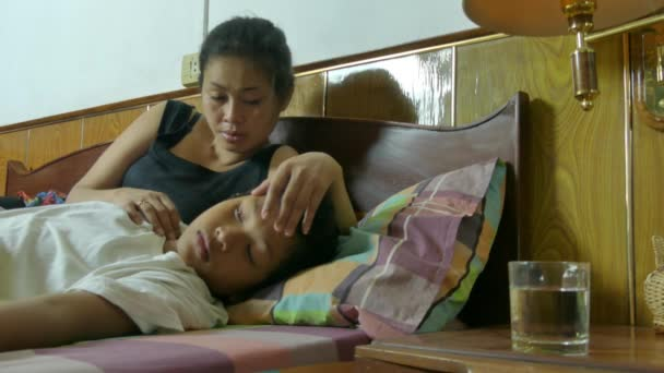 Medium bedside view of a multicultural Asian mother with her sick son