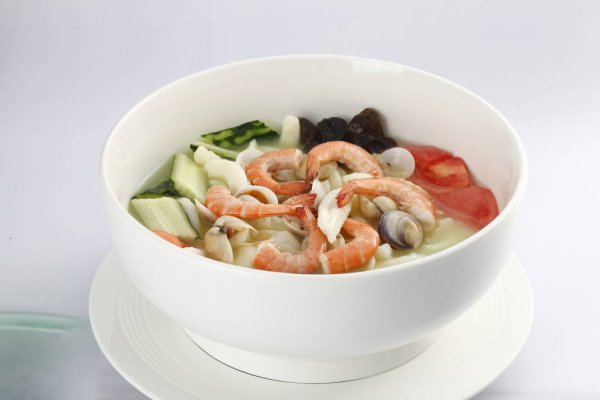 Bowl of seafood noodle soup on kitchen table