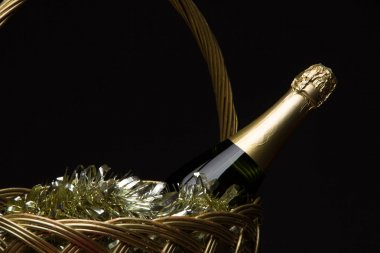 A bottle of champagne in a straw basket with New Year's tinsel a