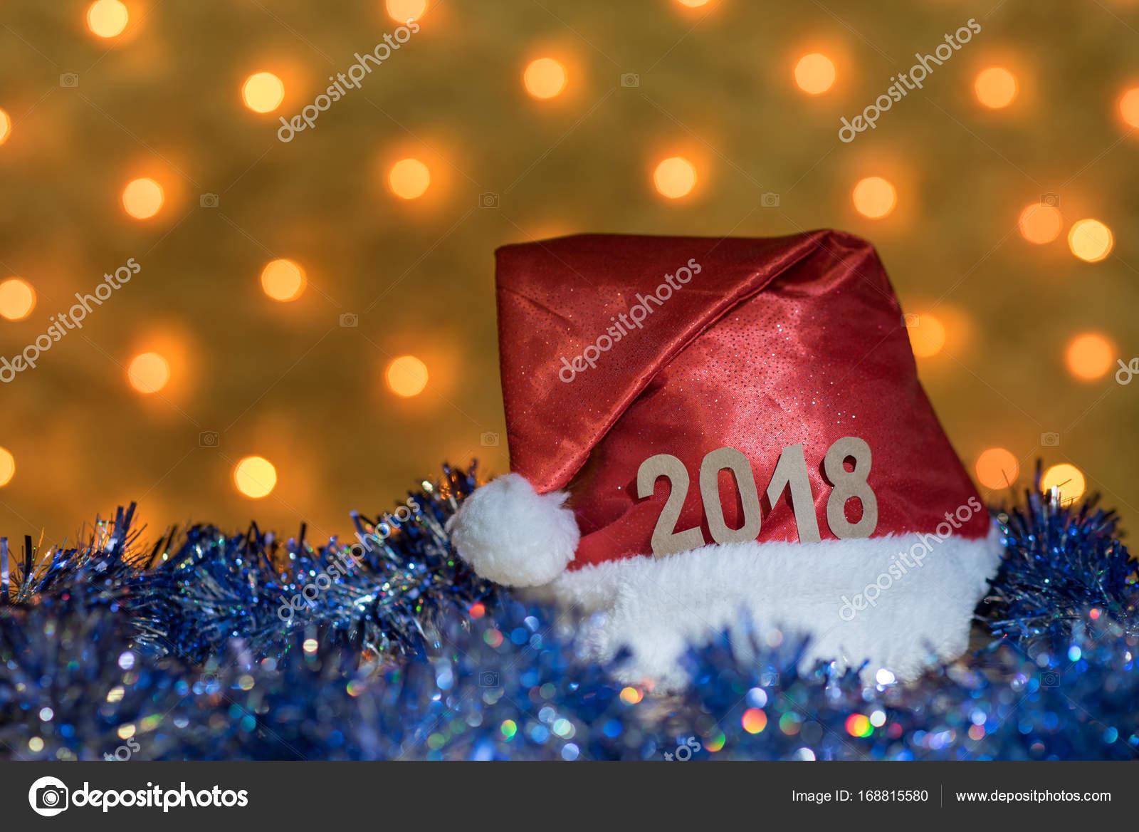 Rote Mütze und blaue Lametta mit Figuren von 2018 auf einem Tisch ...