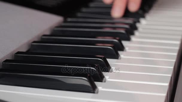 schöne Finger auf weißen und schwarzen Klaviertasten oder ein Synthesizer spielen eine Melodie