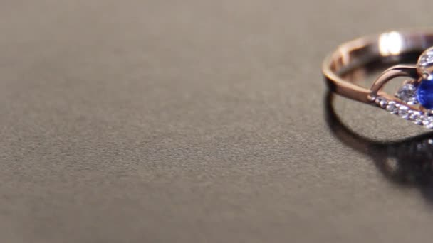 Beautiful engagement female gold ring with precious stones with blue sapphire and white jade on a black background
