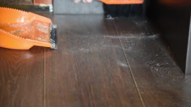 Žena zamete prach na podlaze v domě s oranžovým kartáčů a košťat a přináší pořádek a čistotu