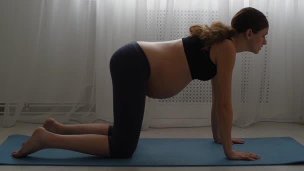 Krásná mladá těhotná žena doma cvičí jógu na koberci. Gymnastika na podložce. Holka se špatným protažením