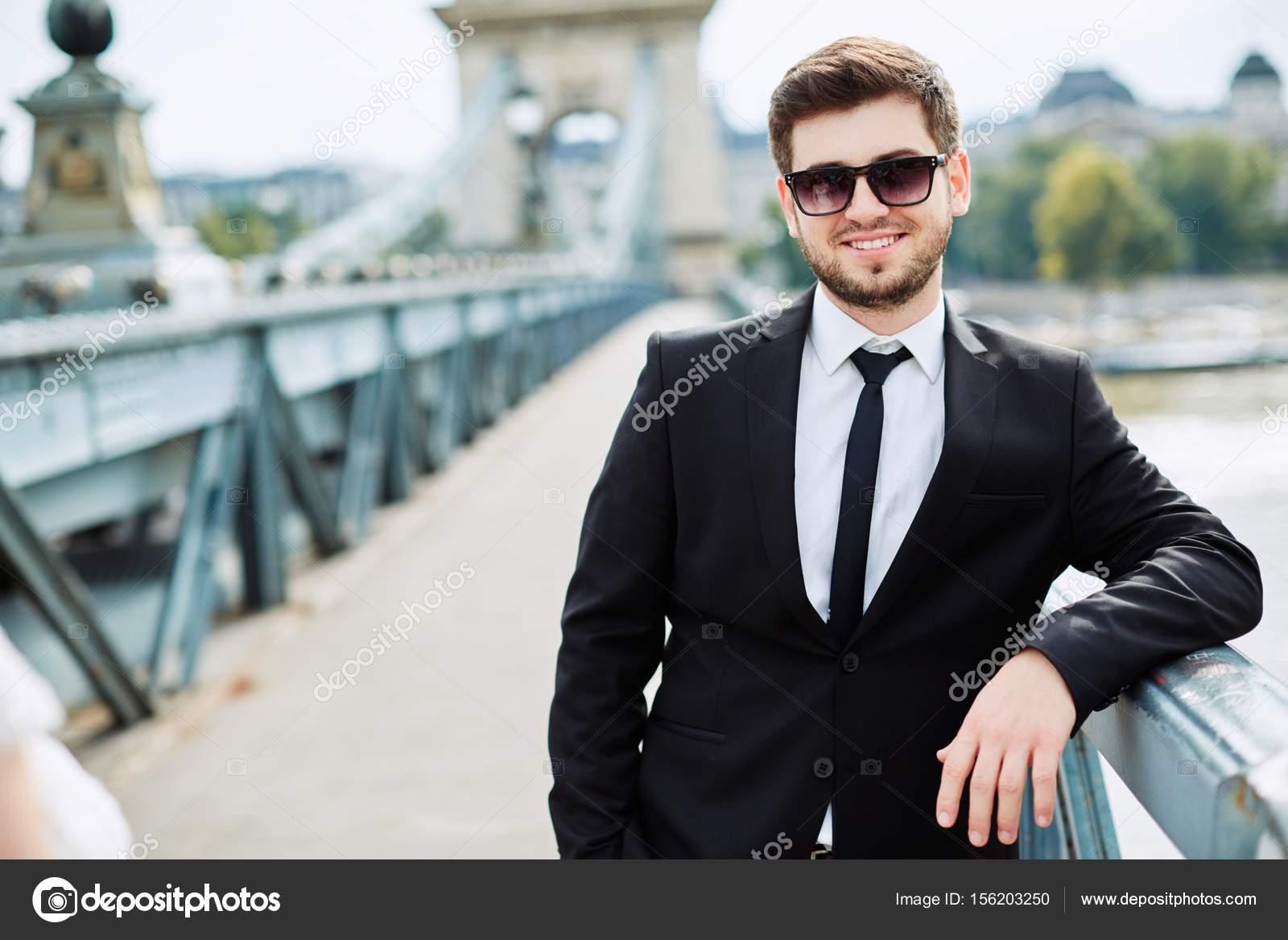 young man leaning on railing on bridge stock photo velesstudio