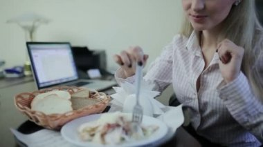 Businesswoman eating at workplace