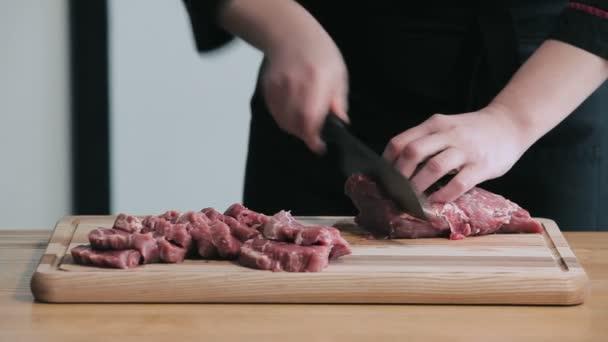 Frauen schneiden rohes Rindfleisch