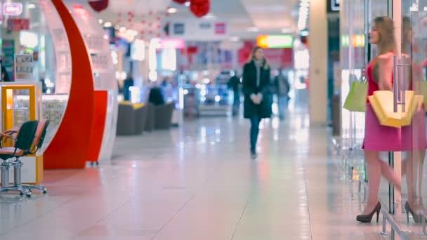 Mladá dívka vyjde z obchodu v obchoďáku. Dívka, rozhlížel se kolem a ponechává v obchodě.