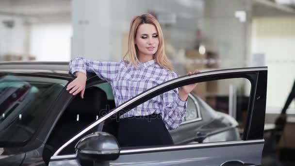 woman posing behind new car