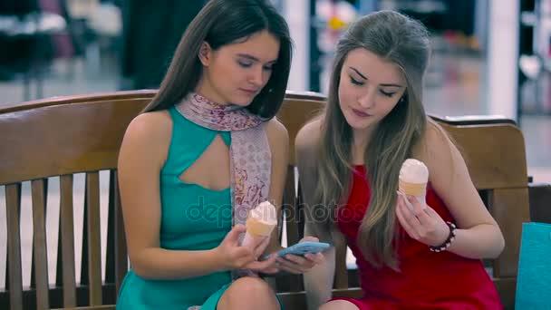 Dvě dívky sedící na lavičce v obchoďáku. Přítelkyně se jíst zmrzlinu.