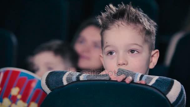 lehnte sich der kleine Junge an die Rückenlehne. der Junge sieht den Film und schreit im Kino.