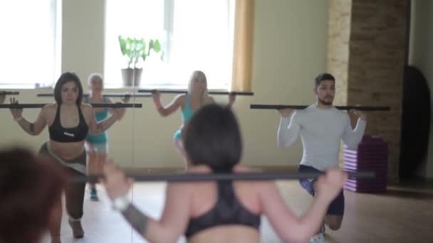 Skupina lidí, kteří dělají cvičení s tyčí