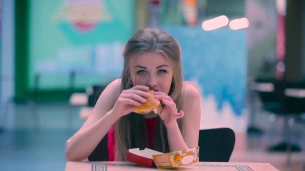 Dívky jsou hladoví. Mladá dívka chaotický jíst humburger v kavárně a otřít ústa rukou