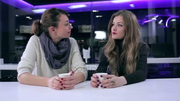 Dvě krásné dívky mluví v kavárně
