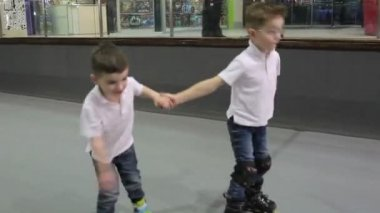 Two little boys riding on the rollers on rollerdrome. The boys smiling and holding hands.