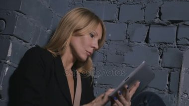 Blonde woman using digital tablet