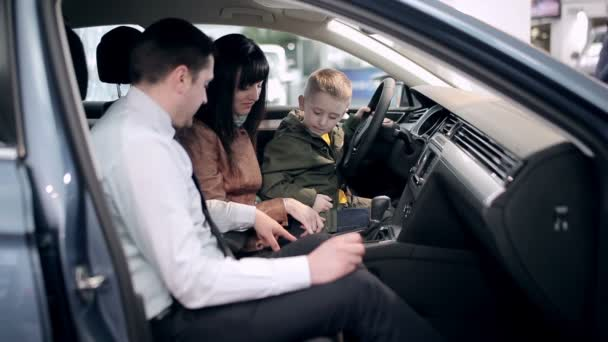 Future driver testing vehicle in dealership. Little boy repeats all actions that salesman shows while sitting on moms hands. Family, potential customers in a car dealership making car purchase.