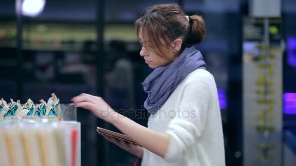Dívka si vybírá produkty s tabletem