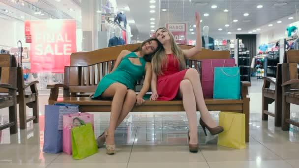 Dívky jsou odpočívá po nakupování na lavičce v obchoďáku.