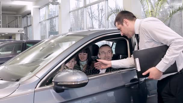 Sales manager advises family in choosing a new car. Family, potential customers in a car dealership making car purchase.