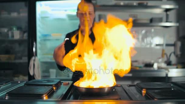 Kuchař dělá flambe s klobásou