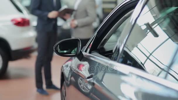 car and blurred customer and salesman