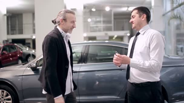Successful deal in the car dealership. Male buying a car from a dealer. Handshake between buyer and seller. Car seller handing over the key to the buyer in car dealership.