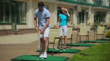 young man and woman play golf on green grass at golf club