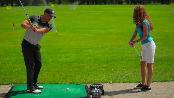 junger Mann und Frau spielen Sie Golf auf dem grünen Rasen im Golf club