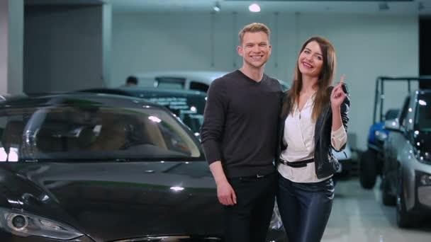 junges Paar mit Schlüssel aus Neuwagen im Autohaus