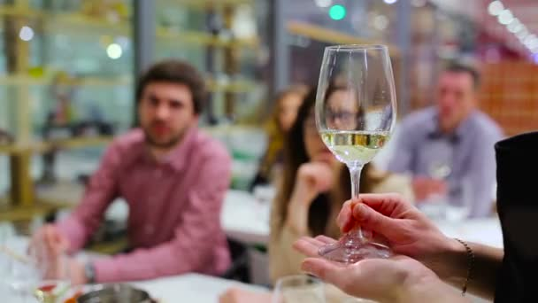 female sommelier holding and moving glass with white wine on wine degustation