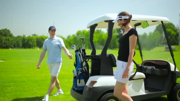 young man and woman with mini golf car on green grass at golf club