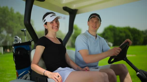 young man and woman in mini golf car on green grass at golf club