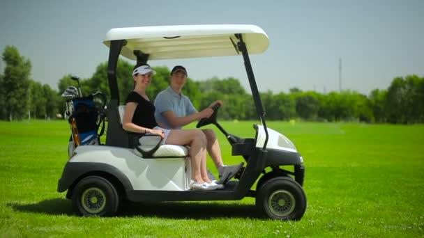 mladý muž a žena v mini autíčko na zelené trávě golfového klubu