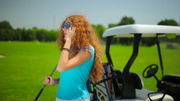 red hair woman in blue shirt using phone on green grass near car in golf club