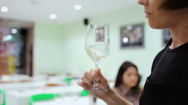 close-up of female sommelier Moving white wine in glass