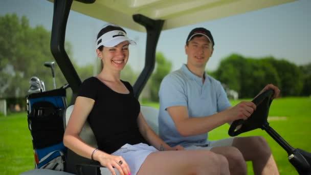 mladý muž a žena v autě minigolf na zelené trávě golfového klubu