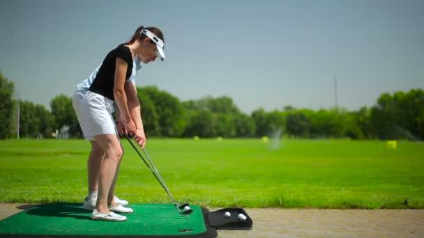 Junge Männer und Frauen spielen Golf auf grünem Gras im Golfclub