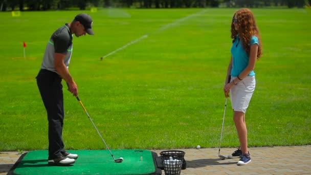 mladý muž a žena hrát golf na zelené trávě golfového klubu